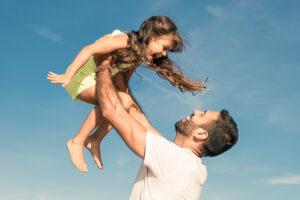 healthy man picking up daughter